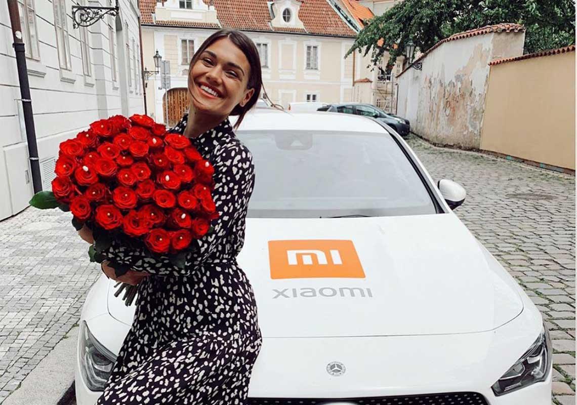 Andrea Kalousová s kyticí růží a Mercedesem s logem Xiaomi